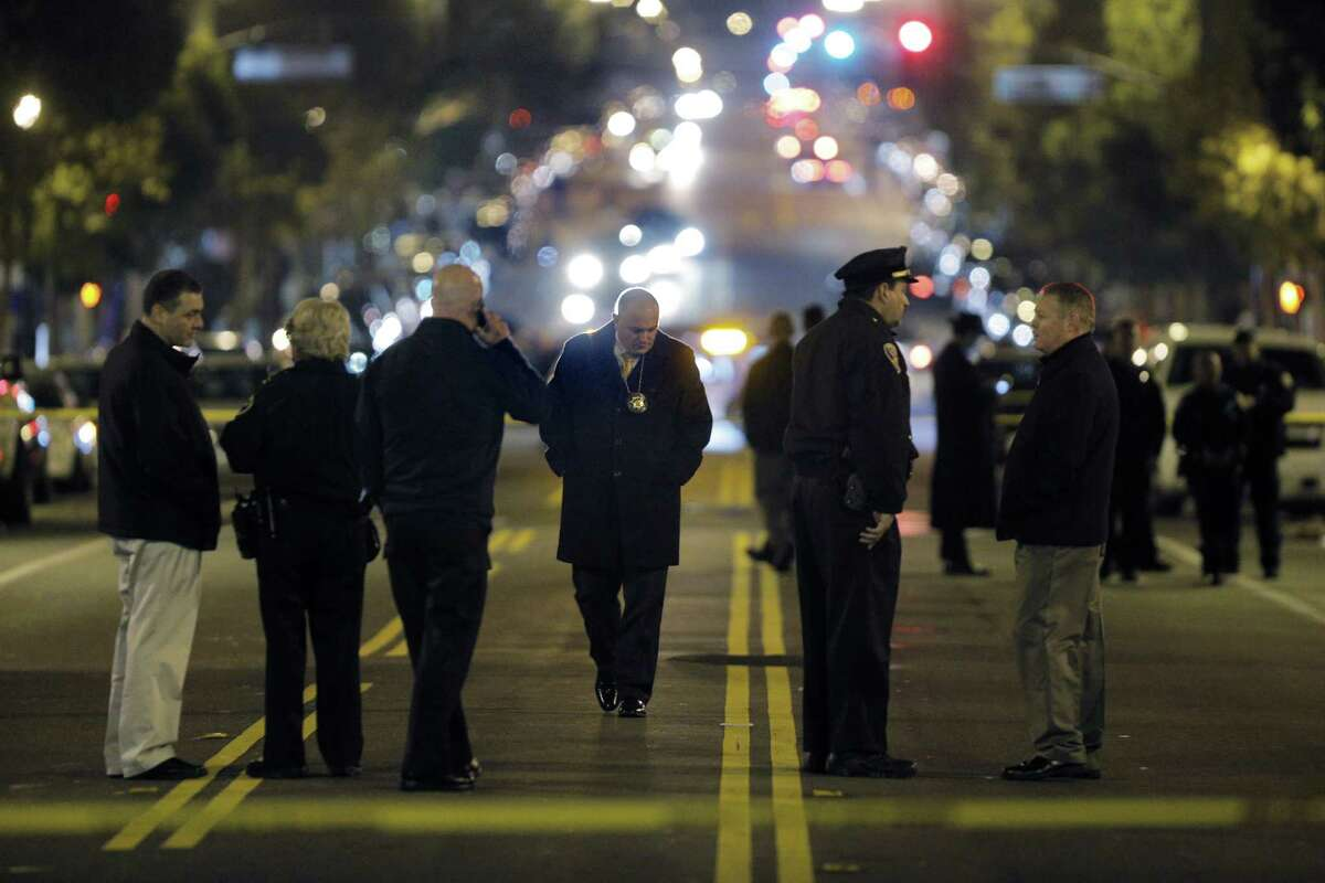 Police investigators gather on Valencia Street after an officer-involved shooting at the San Francisco Police Mission Station in San Francisco, Calif., on Sunday, January 4, 2015.