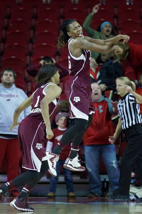 Texas A&M's Achiri Ade, center, leaps as she and Courtney Williams (1) celebrate at the end of an NCAA college basketball game in Fayetteville, Ark., Sunday, Jan. 4, 2015. Texas A&M defeated Arkansas 52-50. (AP Photo/Danny Johnston) Photo: Danny Johnston, STF / AP