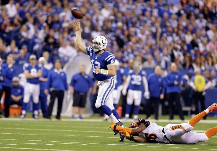 Colts quarterback Andrew Luck gets away from the Bengals' Carlos Dunlap just in time to throw a 36-yard touchdown pass to  Donte Moncrief in the third quarter. Photo: Michael Conroy, STF / AP