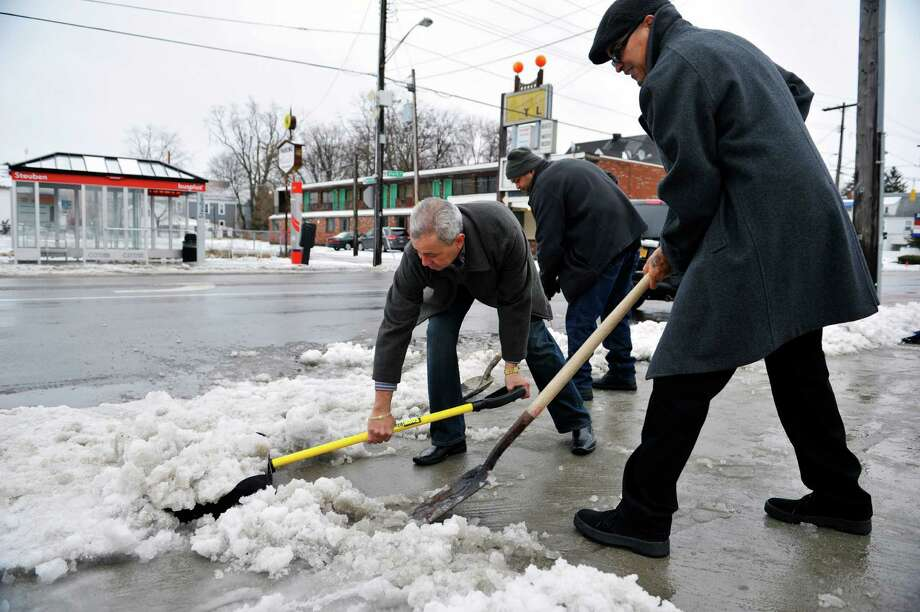 Albert Rivera, left, Gerardo Pedragon, center, and Victor Rodriguez, right, clear slush and ice from the sidewalk outside the Church of God at 920 State St. on Sunday, Jan. 4, 2015, in Schenectady, N.Y. The men were clearing the walkway for church goers.  (Paul Buckowski / Times Union) Photo: Paul Buckowski / 00030071A