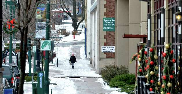 A woman makes her way along snow and ice covered State St. on Sunday, Jan. 4, 2015, in Schenectady, N.Y.  (Paul Buckowski / Times Union) Photo: Paul Buckowski / 00030071A