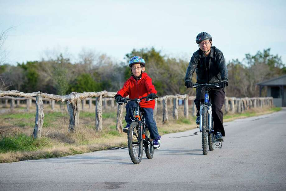 Fengxin Chen, right, and his son Kimmy Chen bike together at Government Canyon State Natural Area in San Antonio, Tx. on Sunday, January 4, 2014. The Chens have been coming to the park for many years and enjoy the natural beauty they said. San Antonio City Council will soon vote on whether or not to annex additional lands in the property mid January. Photo: Matthew Busch, For The San Antonio Express-News / © Matthew Busch