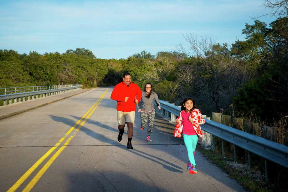 Andrew Adam, his wife Jennifer Adam and their daughter Sienna Adam run together across a bridge at Government Canyon State Natural Area in San Antonio, Tx. on Sunday, January 4, 2014. San Antonio City Council will soon vote on whether or not to annex additional lands in the property mid January. Photo: Matthew Busch, For The San Antonio Express-News / © Matthew Busch