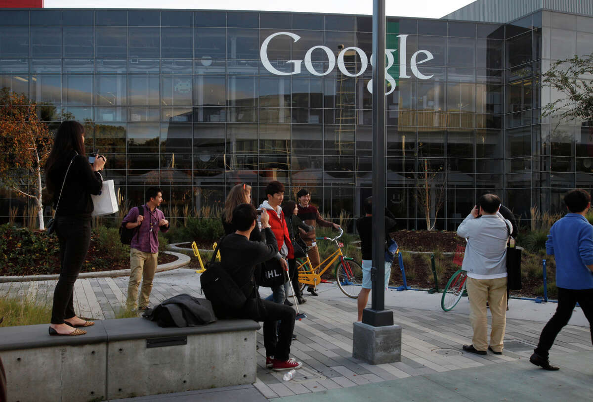 Google's Mountain View headquarters draw visitors who pose for photos. The company's disappointing quarterly profit prompted investors to sell the stock.