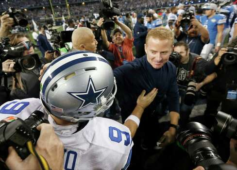 Tony Romo and head coach Jason Garrett greet after an NFL wildcard playoff football win against the Detroit Lions. Photo: Brandon Wade /Associated Press / FR168019 AP