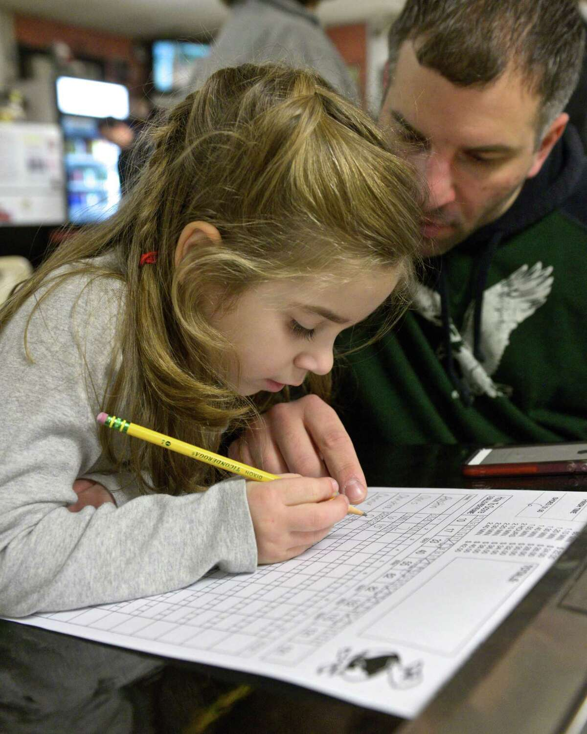 Olivia Caridi, 5, of Brookfield, learns how to keep score in duckpin bowling under the watchful eye of her dad, Chris Caridi during a family outing to Danbury Lanes, one of fifty five or so duck pin bowling lanes left in the United States. The lanes have been on East Hayestown Road since the 1940's. Saturday, December 27, 2014, Danbury, Conn.