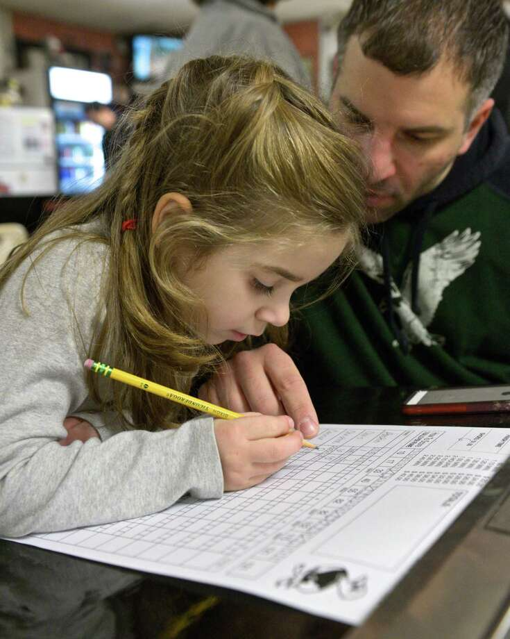 Olivia Caridi, 5, of Brookfield, learns how to keep score in duckpin bowling under the watchful eye of her dad, Chris Caridi during a family outing to Danbury Lanes, one of fifty five or so duck pin bowling lanes left in the United States. The lanes have been on East Hayestown Road since the 1940's. Saturday, December 27, 2014, Danbury, Conn. Photo: H John Voorhees III / The News-Times