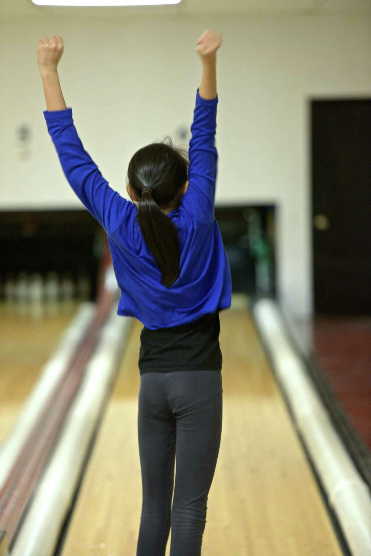 Grace Woleck, 11, of Bethel, signals she is pleased with her roll while duckpin bowling at Danbury Lanes, on Saturday, December 27, 2014, in Danbury, Conn.