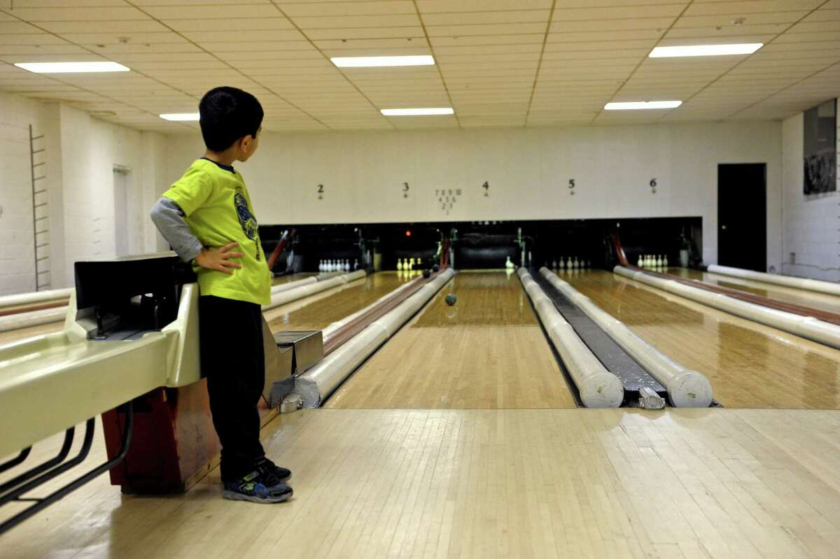 Om Patel, 5, of New Milford, watches his ball slowly roll down the lane while duckpin bowling at Danbury Lanes. Saturday, December 27, 2014, Danbury, Conn. This was panel's second time bowling and he was bowling with his mom.