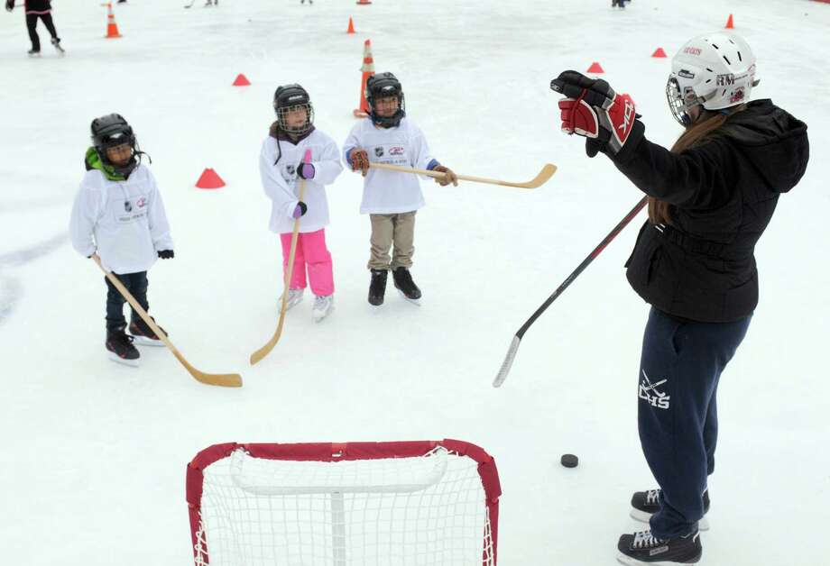 Seventeen-year-old Katy Kennedy a player with the Troy Albany Ice Cats teaches how to shoot on goal during a event designed to provide kids ages 4 to 9 a free experience to try youth hockey at the Empire State Plaza ice rink on Saturday Jan. 3, 2015 in Albany, N.Y. (Michael P. Farrell/Times Union) Photo: Michael P. Farrell / 00029990A