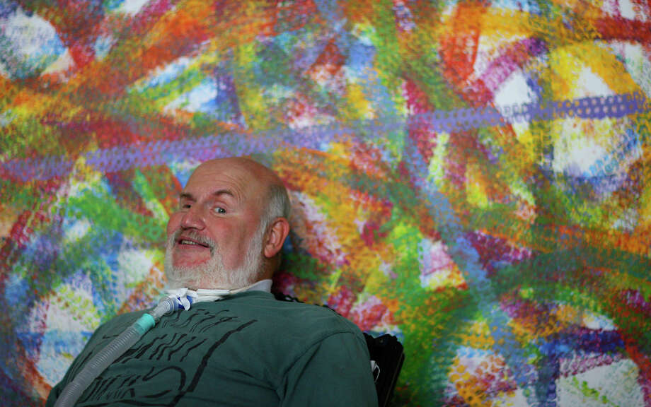 Robert Rehm, at home in 2008, shows artwork he painted with his wheelchair. Rehm was a Jump-Start Theater Co. member. Photo: San Antonio Express-News File Photo / msobhani@express-news.net