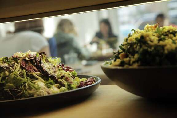 Customers enjoy lunch as seen through the display case at Seed + Salt in San Francisco.