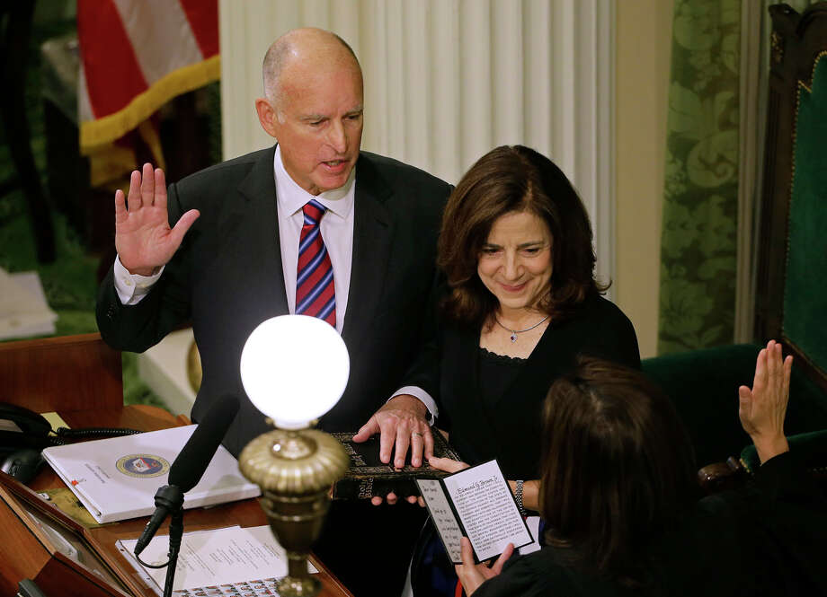 California Gov. Jerry Brown, left, takes the oath of office from Chief Justice of the California Supreme Court Tani Cantil-Sakauye, right, as his wife, Anne Gust Brown, center, looks on during his inauguration at the state Capitol Monday, Jan. 5, 2015, in Sacramento, Calif. When Brown takes the oath of office Monday, it will be the first time a California governor will be sworn in to a fourth term. The 76-year-old Democrat, who held office from 1975 to 1983 before term limits and returned for a third term in 2011, delivered a joint inauguration and state of the state address in the Assembly chamber at the state Capitol. Photo: Eric Risberg, AP / AP