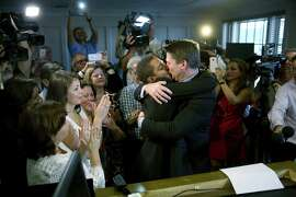 Newlyweds Jeff Delmay (left) and Todd Delmay embrace in the chambers of Circuit Judge Sarah Zabel in Miami.