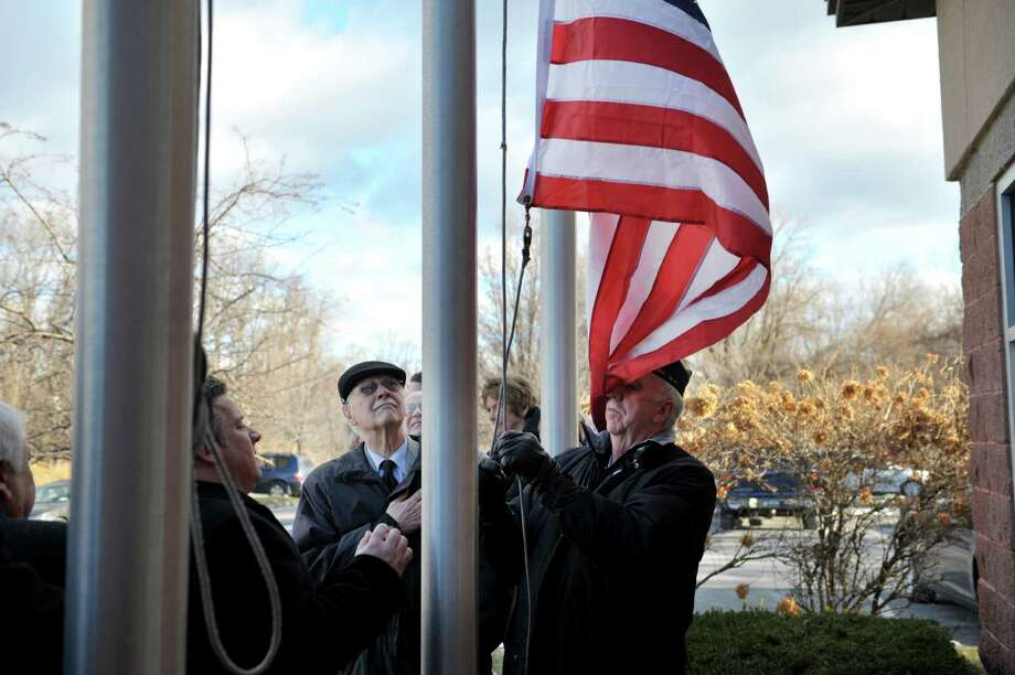 Albany County Executive Dan McCoy, left, Richard Persico, center, and veteran Harvey Martel, right, take part in a  flag raising at an event to honor  Richard's brother, veteran Joseph Persico, at the American Legion Joseph E. Zaloga Post 1520 on Monday, Jan. 5, 2015, in Albany, N.Y.  Martel is also the service officer of the post.   Persico was this month's Albany County Honor-a-Vet recipient.  Persico served in the US Navy.   (Paul Buckowski / Times Union) Photo: Paul Buckowski / 00030066A