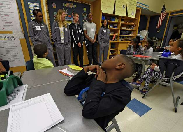 Jayden Henry, center, listens to members of the Siena Men's and Women's basketball team during their visit to the North Albany Academy Monday morning, Jan. 5, 2015, in Albany, N.Y., to teach Capital Region students the importance of hard work and commitment. The appearance was part of the annual Siena Athletic Blue Shield of Northeastern New York Saints in the Community Program.  (Skip Dickstein/Times Union) Photo: SKIP DICKSTEIN / 00030064A