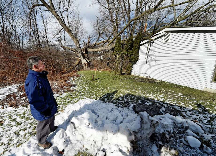Frank Doberman looks at the damage done when a tree landed on his building at Karner Psychological Associates Monday morning, Jan. 5, 2015, in Guilderland, N.Y.     (Skip Dickstein/Times Union) Photo: SKIP DICKSTEIN