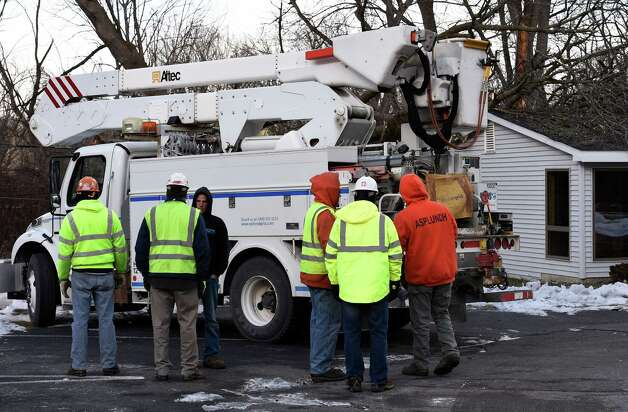 National Grid and Asplundh workers gather at the site of a tree on to a building at Karner Psychological Associates Monday morning Jan. 5, 2015, in Guilderland, N.Y.     (Skip Dickstein/Times Union) Photo: SKIP DICKSTEIN