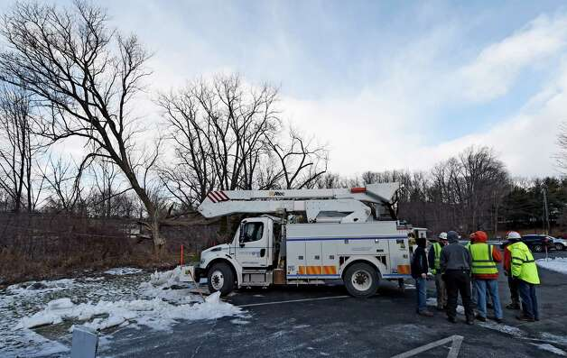 National Grid and Asplundh workers gather at the site where a tree fell on to a building at Karner Psychological Associates Monday morning, Jan. 5, 2015, in Guilderland, N.Y.   (Skip Dickstein/Times Union) Photo: SKIP DICKSTEIN