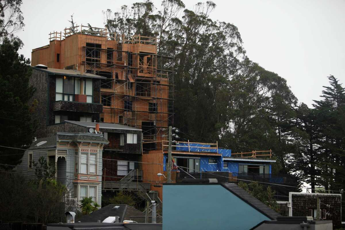 A six-story building is under construction on States Street amid Corona Heights' cottages, staircases and winding lanes.