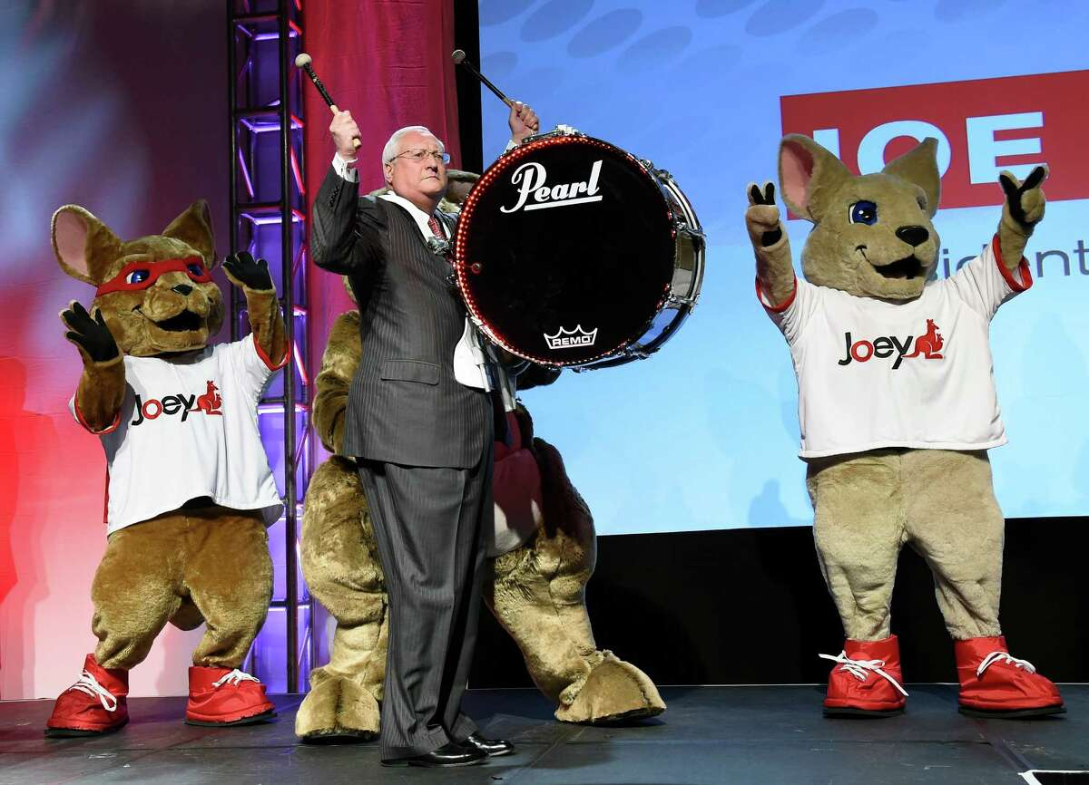 LAS VEGAS, NV - JANUARY 05: DISH President and CEO Joe Clayton makes his entrance playing a drum with kangaroo characters at a press event for DISH at the Mandalay Bay Convention Center for the 2015 International CES on January 5, 2015 in Las Vegas, Nevada. CES, the world's largest annual consumer technology trade show, runs from January 7-10 and is expected to feature 3,200 exhibitors showing off their latest products and services to about 150,000 attendees. (Photo by Ethan Miller/Getty Images) *** BESTPIX ***