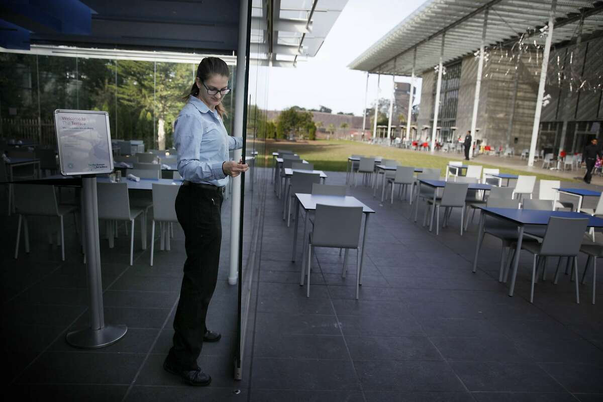Vanessa Schagerer, supervisor The Terrance, moves a panel of the retractable glass wall as she demonstrates how the restaurant has the option of folding open its walls at the California Academy of Sciences on Monday, January 5, 2015 in San Francisco, Calif.