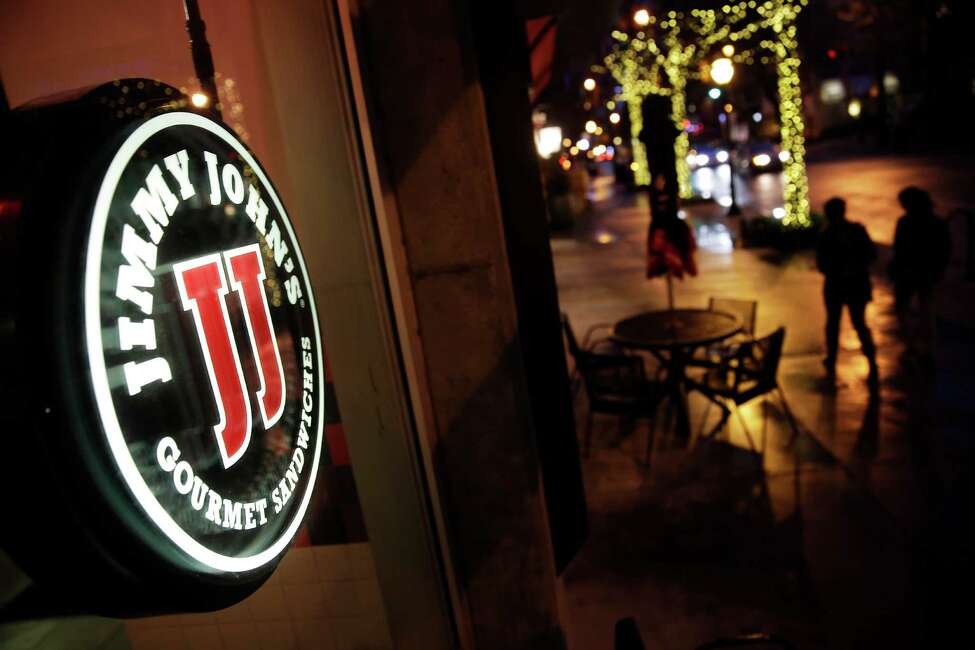 Pedestrians pass by a Jimmy John?'s sandwich shop, Friday, Jan. 2, 2015, in Atlanta. A lawsuit targeting the fast-food sandwich chain has put scrutiny on agreements banning low- and middle-wage workers from competing against their former employers. (AP Photo/David Goldman) ORG XMIT: GADG201