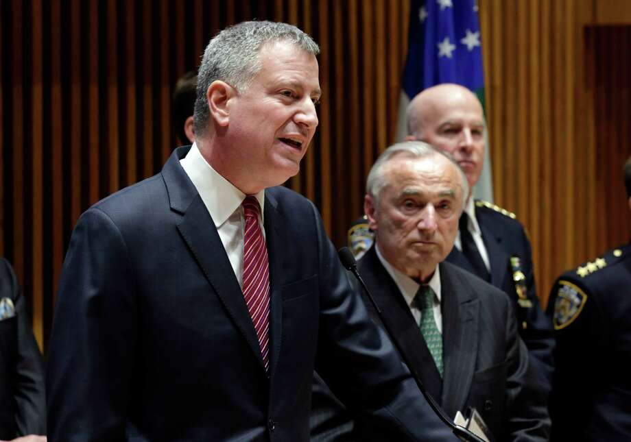 "New York Mayor Bill de Blasio, left, accompanied by New York City Police Commissioner William Bratton, center, addresses a news conference at New York City Police headquarters, Monday, Jan. 5, 2015. De Blasio says it was ""disrespectful"" that some NYPD officers turned their backs to him during a pair of funerals for slain police officers. (AP Photo/Richard Drew) ORG XMIT: NYRD115 Photo: Richard Drew / AP"
