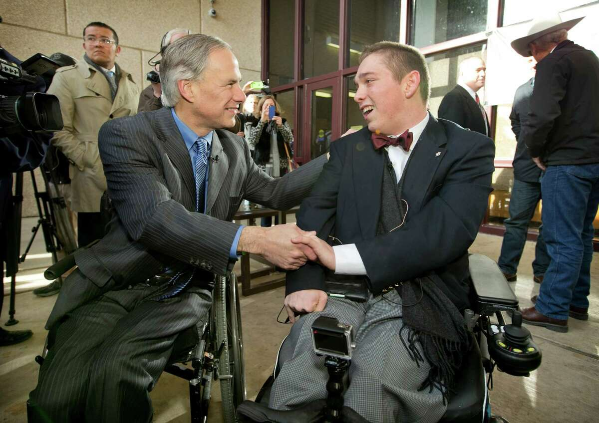 Texas Gov.-elect Greg Abbott, left, congratulates Austin High School student Archer Hadley on Monday over his efforts to fund the installation of  wheelchair-accessible doors at the school.
