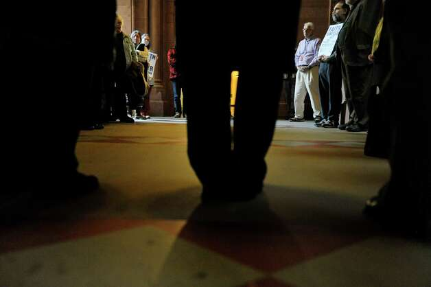 People take part in a prayer circle during a rally at the Capitol on Monday, Jan. 5, 2015, in Albany, N.Y.  The rally was held to call on legislators to move forward with a policy agenda that prioritizes good jobs with living wages.  (Paul Buckowski / Times Union) Photo: Paul Buckowski / 00030075A