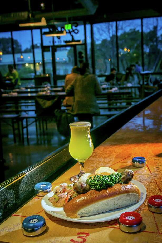 At Hog's Apothecary in Oakland, the specialties are beer and pig, including a Manifesto, a Belgian-style Witbier, with the sausage sandwich. Photo: John Storey / Special To The Chronicle / ONLINE_YES