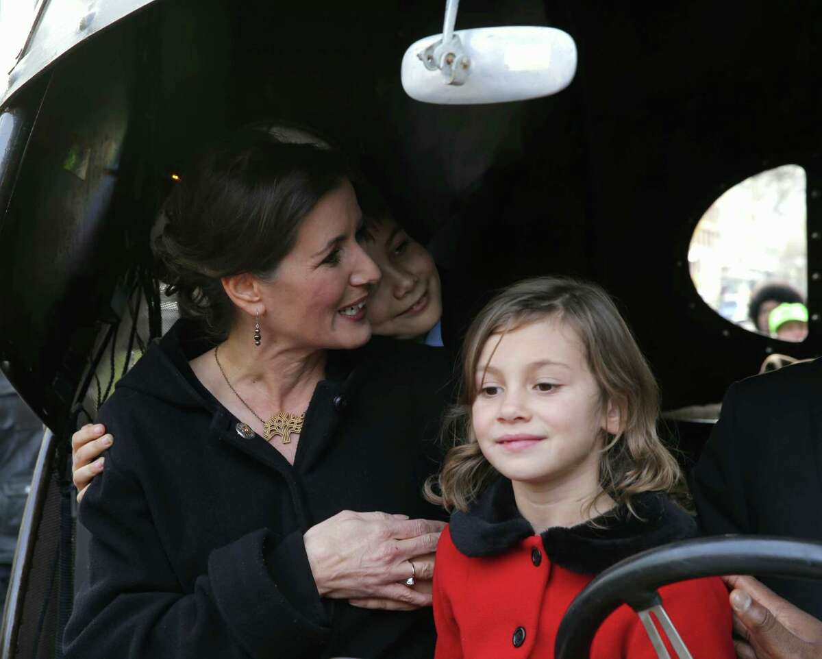 Oakland Mayor-elect Libby Schaaf gets a hug from her son Dominic, 9, with her daughter Lena, 7, in an art car at the Paramount Theater in Oakland, Calif., for her inauguration on Monday, January 5, 2015.