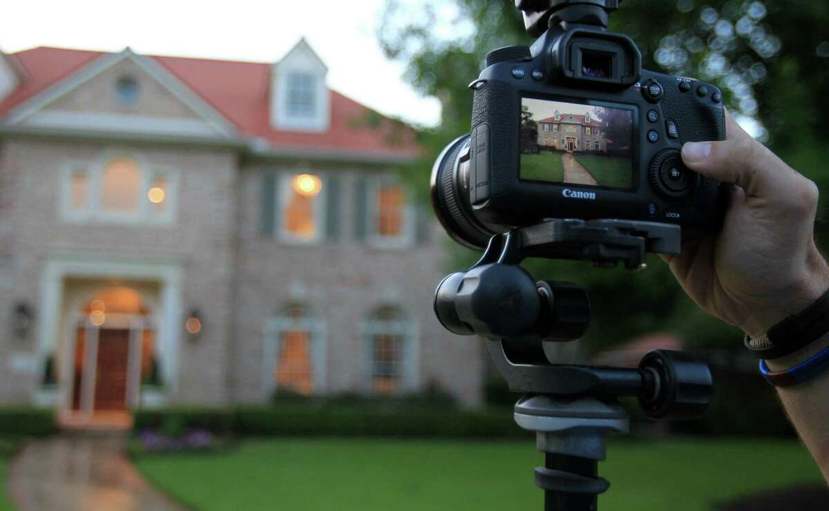 TK Images real estate photographer Bill Krampitz views his exterior shots while photographing a multimillion dollar home on May 15, 2014, in Houston, Tx. ( Mayra Beltran / Houston Chronicle )