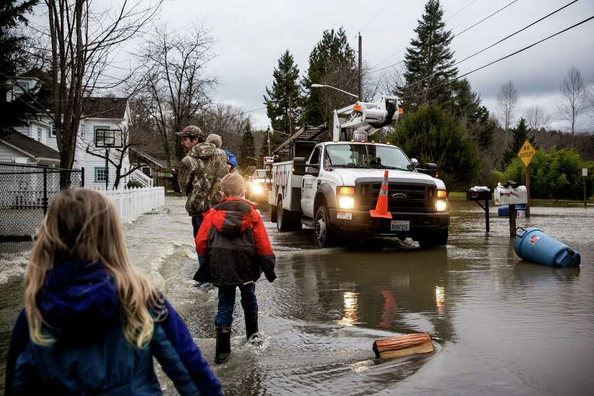 Families walk through a heavily-flooded neighborhood on the banks of the Snoqualmie River Monday, January 5, 2015, in Snoqualmie, Washington. Floods and landslides closed several roads and forced evacuations across Western Washington following a heavy storm in the early morning.