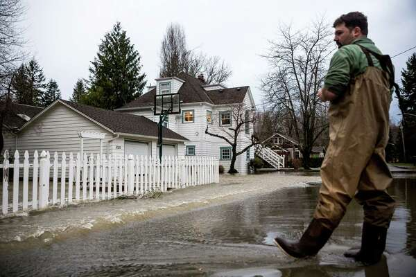 Brian Shuck, right, looks on as Snoqualmie River water pushes through his fence and into his newly-purchased home Monday, January 5, 2015, in Snoqualmie, Washington. Thanks to early email alerts about the flooding, Shuck managed to get most of his belongings up off of the floor before the nearby riverbank overflowed. Floods and landslides closed several roads and forced evacuations across Western Washington following a heavy storm in the early morning.