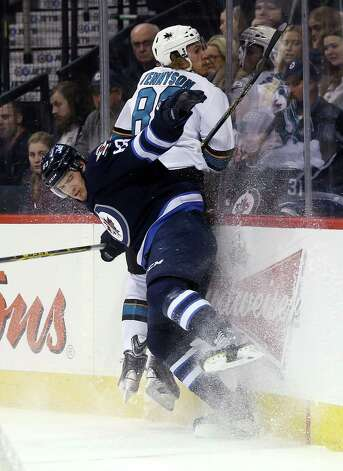 Winnipeg Jets' Ben Chiarot (63) hits San Jose Sharks' Matt Tennyson (80) during the first period of an NHL hockey game Monday, Jan. 5, 2015, in Winnipeg, Manitoba. (AP Photo/The Canadian Press, Trevor Hagan) ORG XMIT: WPGT105 Photo: Trevor Hagan / The Canadian Press