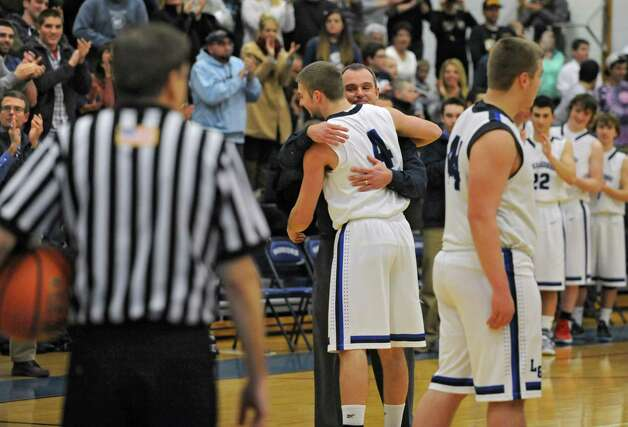 Lake George's Joel Wincowski gets a hug from coach Dave Jones after making a career point total of 2,000 during a basketball game against Ticonderoga on Monday, Jan. 5, 2015 in Lake George, N.Y. (Lori Van Buren / Times Union) Photo: Lori Van Buren / 00030073A