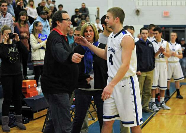 Lake George's Joel Wincowski gets a hug his dad Joel after making a career point total of 2,000 during a basketball game against Ticonderoga on Monday, Jan. 5, 2015 in Lake George, N.Y. His mother Carol stands in center. (Lori Van Buren / Times Union) Photo: Lori Van Buren / 00030073A