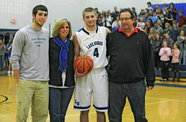 Lake George's Joel Wincowski stands with his brother Ethan, left, mother Carol and father Joel after making a career point total of 2,000 during a basketball game against Ticonderoga on Monday, Jan. 5, 2015 in Lake George, N.Y. (Lori Van Buren / Times Union) Photo: Lori Van Buren / 00030073A