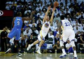 Golden State Warriors' Klay Thompson steals a pass by Oklahoma City Thunder's Serge Ibaka in 1st quarter during NBA game at Oracle Arena in Oakland, Calif. on Monday, January 5, 2015.