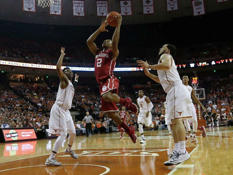 Dinjiyl Walker leaps to the basket between Isaiah Taylor (1)and Javan Felix (3) at the Frank Erwin Center. Oklahoma beat Texas, 70-49. Photo: Chris Covatta /Getty Images / 2015 Getty Images