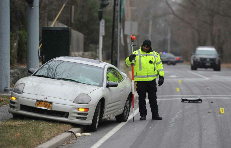 Police examine the scene where a 51 year old female resident of Elmsford, N.Y. was struck and killed by a car as she crossed King St. at Anderson Hill Rd. in Greenwich, Conn. on Tuesday, Jan. 6, 2015. The woman was reportedly exiting a Westchester County mass transportation Bee-Line bus with a co-worker  and was hit by a passenger car while crossing King St. Photo: Tyler Sizemore / Greenwich Time