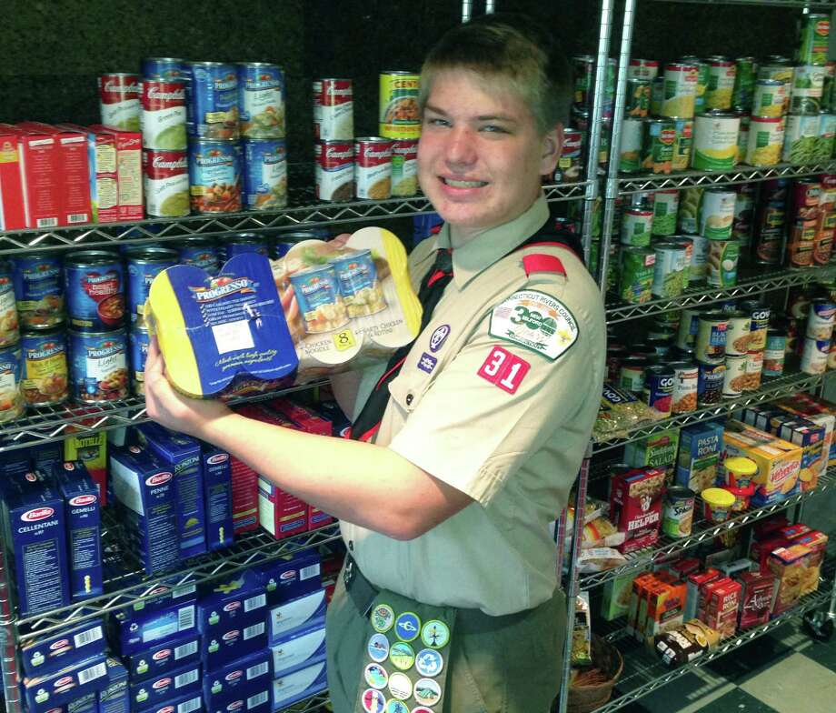 Eagle Scout Pete Kivela of New Milford poses for a keepsake photo in the relocated food pantry at Bridgewater Congregational Church. For more photos, visit www.newmilfordspectrum.com. 2014  Courtesy of the Kivela family Photo: Contributed Photo / The News-Times Contributed