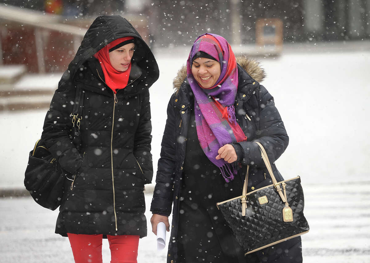 Anna Hashem, left, and Mona Al Nasser, both of Bridgeport, walk along Main Street in Bridgeport, Conn. as snow begins to accumulate on Tuesday, January 6, 2015.