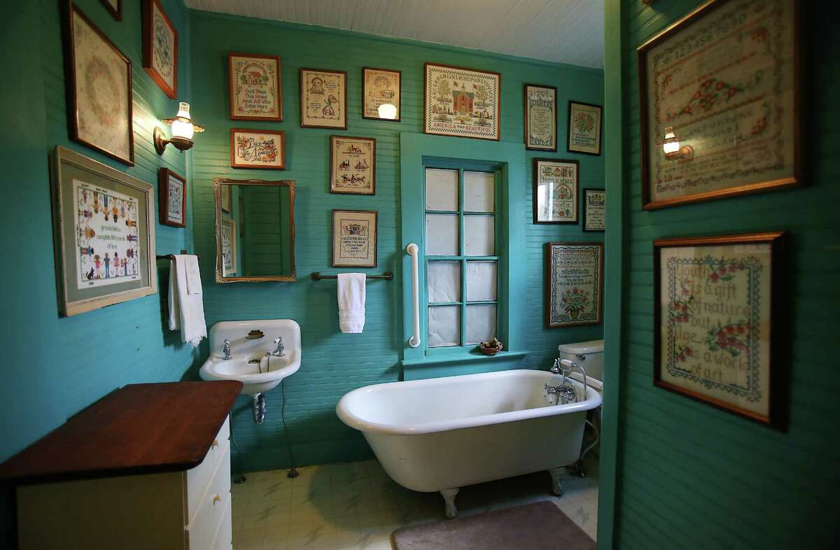 Cross-stitching framed in the bathroom resides on bold turquoise-hued walls in the Windles' 1,600-square-foot home, which was built in 1887.