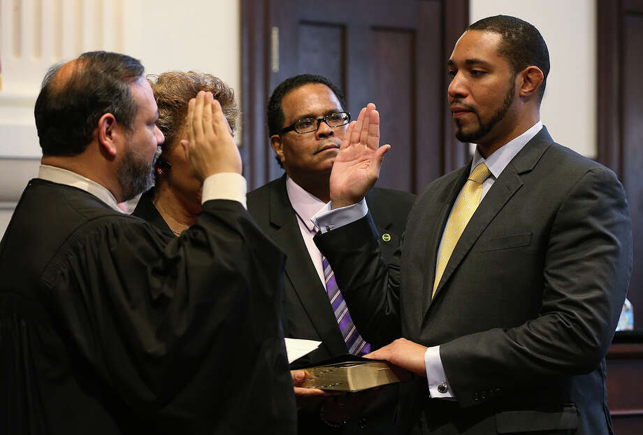 Tommy Calvert, right, is sworn-in as Bexar County Commissioner of Precinct 4, by 379th Criminal District Court Judge Ron Rangel during a commissioners meeting in the Double Height Courtroom at the Bexar County Courthouse, Tuesday, Jan. 6, 2015. Calvert is the county's first black commissioner. In the center is his father, T.C. Calvert. Photo: JERRY LARA, San Antonio Express-News / © 2015 San Antonio Express-News