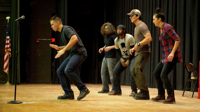STOMP cast members, from left, Eric Fay, Mike Hall, MJ Jackson, John Angeles, and Kris Lee perform at Cloonan Middle School on Tuesday, January 6, 2015. The cast members performed for students, participated in a question and answer session, and promoted their upcoming show at the Palace Theatre.