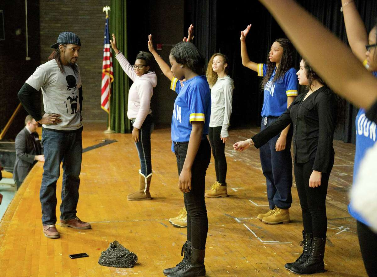 STOMP cast member M.J. Jackson gives tips to the Cloonan Middle School drill team after performing at the school Tuesday, January 6, 2015.