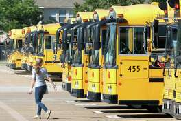 A bus driver walks past a line of buses at one of Katy Independent School District bus barns last year. The district has the sixth largest school bus fleet in Texas.