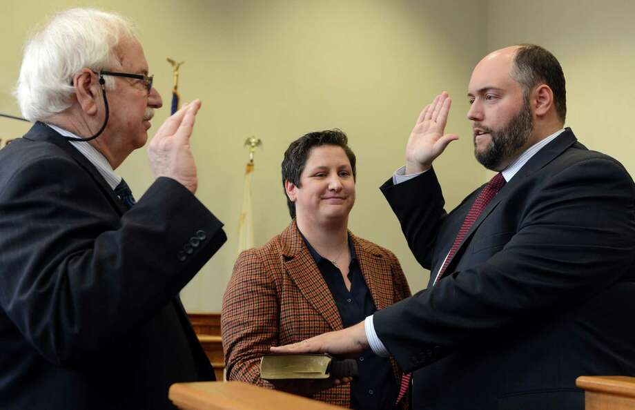Outgoing Probate Judge Clifford D. Hoyle swears in his son Clifford P. Hoyle as the new Probate Judge for the Derby Probate District, as his daughter-in-law Jackie holds the Bible, Tuesday, Jan. 6, 2015, in the Aldermanic Chambers at Ansonia City Hall. Photo: Autumn Driscoll / Connecticut Post